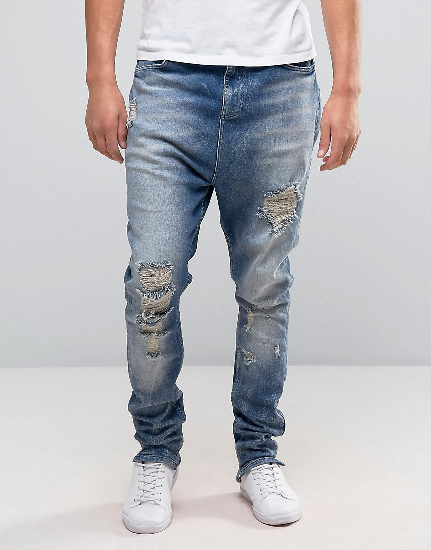 ASOS Drop Crotch Stacked Jeans With Rips And Bleaching In Mid Blue - Mid wash