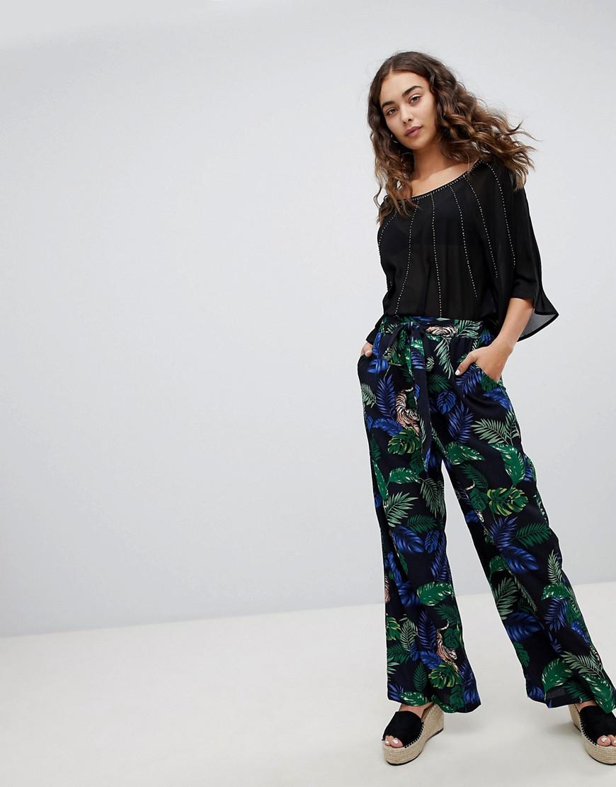 Pantalones de pernera ancha con estampado de tigres y hojas de QED London
