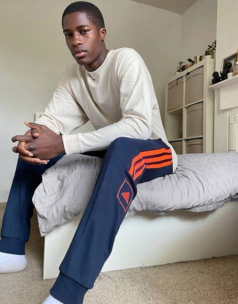 adidas skinny 3 stripe joggers in navy and orange