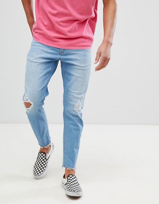 ASOS DESIGN – Ljusblå avsmalnande jeans med stretch och slitna detaljer