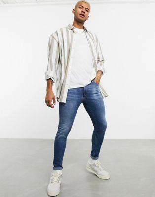 ASOS DESIGN – Spray-on-Jeans aus Power-Stretch-Denim in verwaschenem Mittelblau
