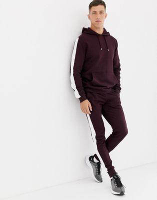 ASOS DESIGN - Survêtement avec hoodie et pantalon ajusté avec bandes sur les côtés - Bordeaux