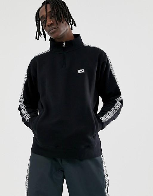 Obey Bridges Svart sweatshirt med 1 4 dragkedja och ränder på sidan