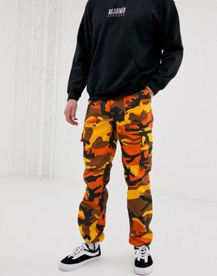 Reclaimed Vintage - Revived - Pantalon cargo à motif camouflage - Orange