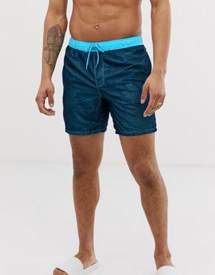 Shorts de baño azules de largo medio con malla superpuesta de ASOS