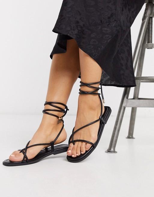 Truffle Collection – Platta sandaler med fyrkantig tå och knytning runt benet